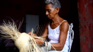 Cuban woman in poor house making a straw hat to be sold to tourists in souvenir stands