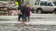 More weather warnings issued by Met Office ENGLAND Cumbria Appleby EXT Woman along in ankle deep floodwater with shopping bags Man sweeping water...