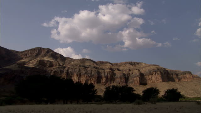 Cumulus clouds float above a rock formation lined with African Acacias. Available in HD.