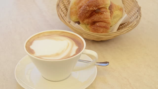 MS Cup of cappuccino cafe and croissant on table / Pietrasanta, Tuscany, Italy