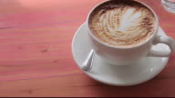 HA Cup of cappuccino sitting on wooden table top / Los Angeles, California, United States