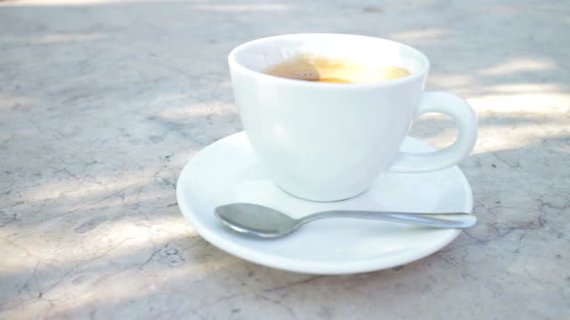 Cup of fresh coffee on a cafe table outdoors