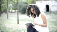 Curly hair female with touchpad learning in nature
