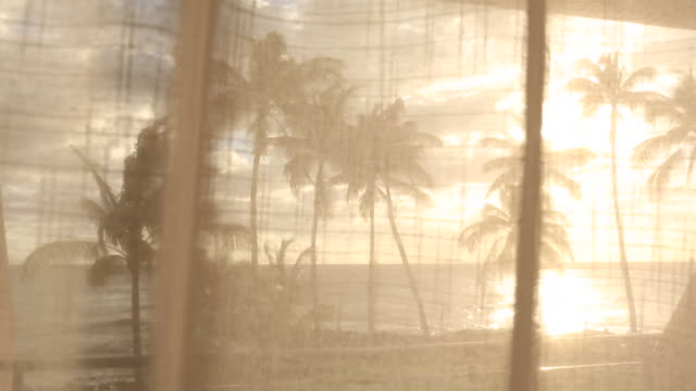 Curtains inside of a hotel room blowing in the wind at sunset in Hawaii