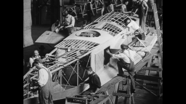 Curtiss airplane factory at Garden City New York where Curtiss NC class seaplanes are being manufactured / crane hoisting a V12 Liberty engine