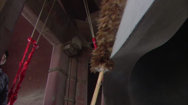 A custodian dusts a huge bell in a bell tower.