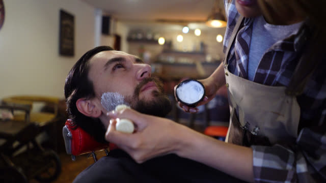 Customer at a barber shop getting a shave