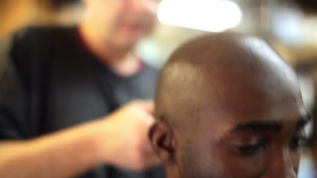 Customer chats and stares ahead while barber trims and shaves his head in local barbershop