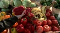 Customer checks damaged vegetables and picks a red bell pepper