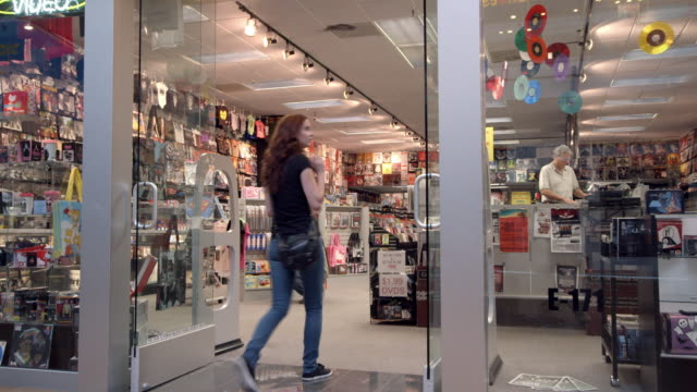 WS TS customer enters record store in mall selling records and t-shirts and novelty items with store manager on elevated cash register platform / Palm Desert, California, USA