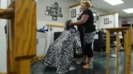 A customer gets her hair washed and cut at Guys Gals Salon in Princeton Illinois on July 16 Wide shot of an elderly white female getting her hair...