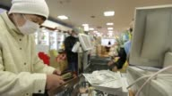 A customer hands over Japanese 1000 yen banknotes while making a purchase at a checkout counter of a Sankei Super KK supermarket in Tokyo Japan on...