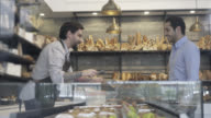 Customer looking at options in the bakery and salesman serving