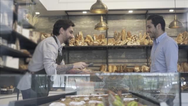 Kunden suchen auf Optionen in der Bäckerei und Verkäufer tätig