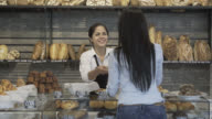 Customer ordering in the bakery counter and saleswoman helping her