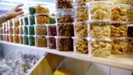 Customer purchases dried fruits and nuts in grocery