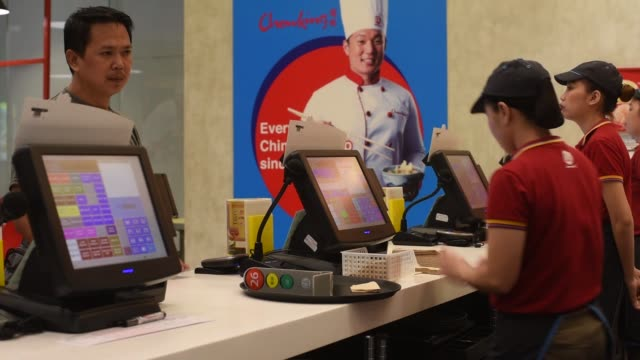 A customer stands at the counter of a Chowking Food Corp Chinese restaurant operated by Jollibee Foods Corp in the Bonifacio Global City triangle...