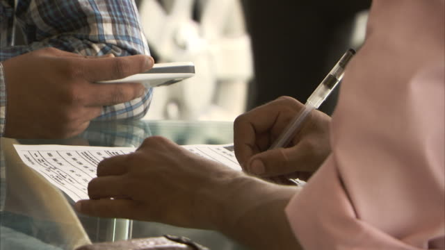 A customer studies his phone while a car salesman fills out paperwork.