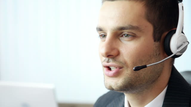 Customer support operator smiling, speaking, looking at camera, in office