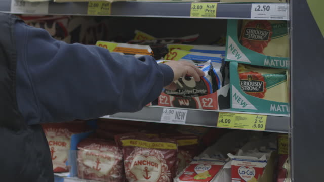 Customers browse various brands of cheese at a large UK supermarket.