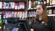 Customers can pay using their fingertips at store in London ENGLAND London Brunel University INT Man buying bottle of water at counter in supermarket...