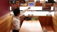 Customers dine in booths inside a Kura Corp sushi restaurant in Kaizuka Osaka Japan on Thursday Aug 17 Dishes of sushi move along a conveyor as a...