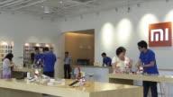 Customers examine Xiaomi mobile phones in the demo room at Xiaomi headquarters in Beijing China on June 3 Xiaomi mobile phones on display