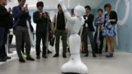 Customers interact with the humanoid robot Pepper developed by SoftBank Corp s Aldebaran Robotics SA unit at a SoftBank store in Tokyo Japan on...