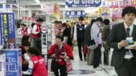 Customers look at refrigerators left and washing machines at a Bic Camera Inc electronics store in Tokyo Japan An employee assists customers...