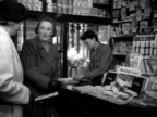 Customers purchase local newspapers in a newsagents 1952