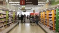 Customers push their shopping carts beneath promotional signs offering great prices as they browse for goods inside a Sainsburys supermarket store...