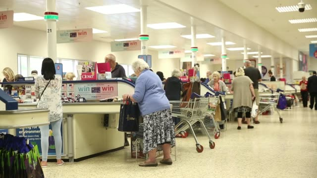 Customers queue to pay for the shopping at check out desks inside a Tesco Extra Supermarket operated by Tesco Plc in London UK on Tuesday July 1 A...