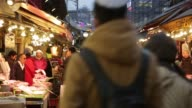 Customers shop for food at the Ameya Yokocho market at dusk in the Ueno district of Tokyo Japan on Monday March 23 A customer left shops for seafood...