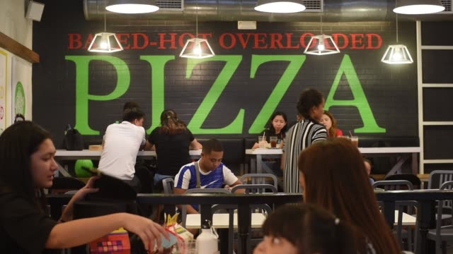 Customers sit at a Greenwich Pizzeria operated by Jollibee Foods Corp in the Bonifacio Global City triangle area of Manila the Philippines on...