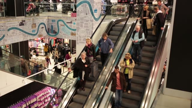 Customers stand on escalators whilst shopping inside a Primark store on Oxford Street in central London Pedestrians pass the entrance to a Primark...