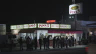 WS Customers standing outside of Pink's Hot Dogs as traffic moves along La Brea Avenue / Los Angeles, California, United States