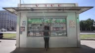 Customers stands at the service window of a traditional food and beverage kiosk which sells items including soft drinks on street in Moscow Russia on...