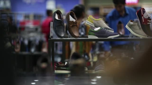 WS customers walk down a staircase in the store MS customers walk past sunglasses on display WS cosmetics counters WS customers browse men's shoes MS...