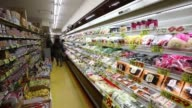 Customers walk through a supermarket in Tokyo Shoppers browse vegetables at a supermarket in Tokyo Tracking shot down a supermarket aisle stopping at...