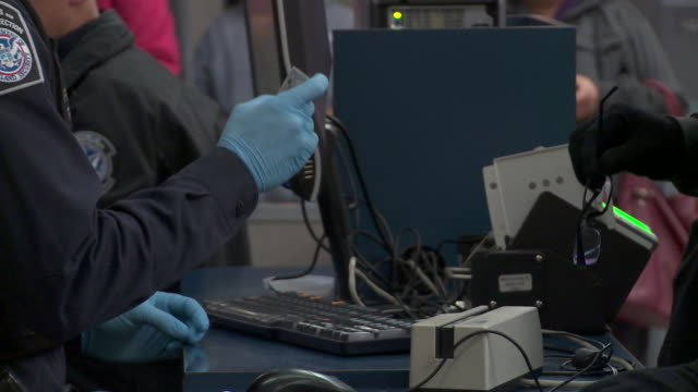 / Customs Border Protection officer checking documents of people entering US