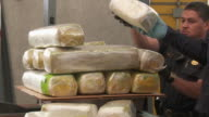 / Customs Border Protection officers confiscate illegal drugs found in vehicle crossing border / weighing drugs on scale / stacking drugs on cart /...