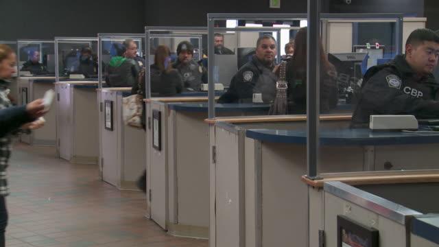 / Customs officers screen pedestrians entering US