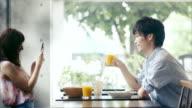 Süße asiatische Paar mit Smartphone im Café