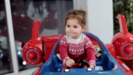 cute baby girl driving in toy airplane and smiling