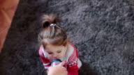 cute baby girl in christmas clothing drinking water from bottle