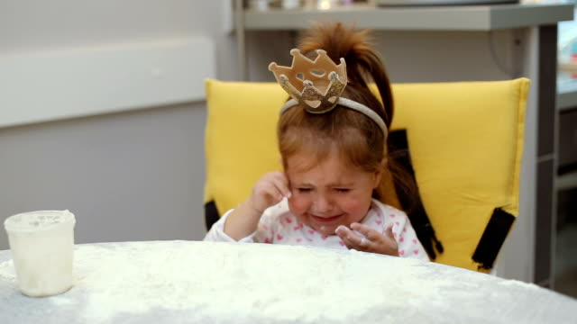 Cute baby girl playing with flour on a table and wearing a crown