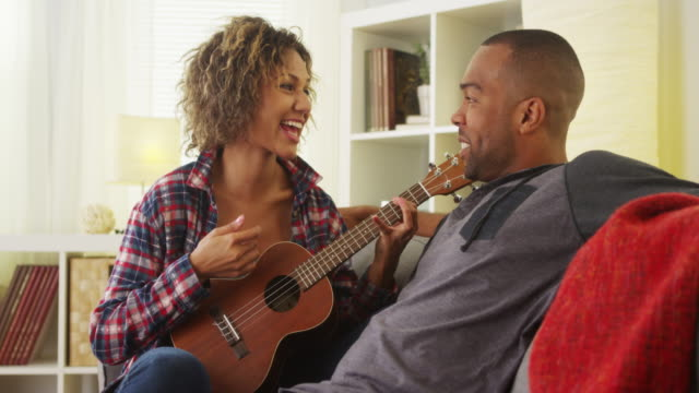 Cute black girlfriend serenading her boyfriend with ukulele