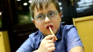 Cute boy eating french fries in restaurant