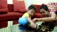 Cute boy with mother learn to count money at home