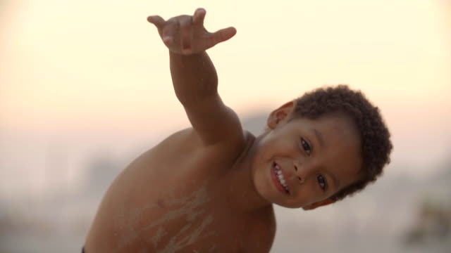 Cute Brazilian boy dances and plays in the sand on Copacabana Beach